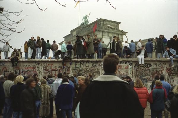 Menschen stehen vor und auf der Mauer am Brandenburger Tor nach der Wende vom 9. November 1989.