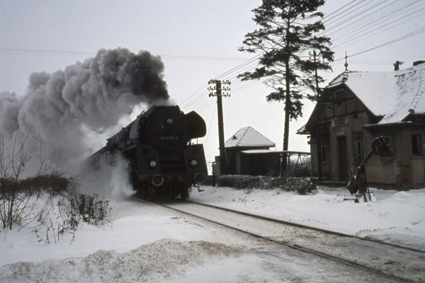 Ein Zug geführt von einer Schnellzugdampflokomotive der Baureihe (BR) 01 1518-8 fährt vorbei an einem verschneiten Haus am Bahnübergang bei Triptis.