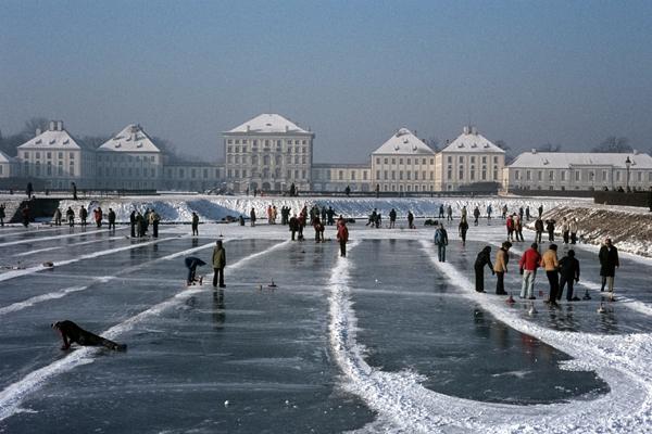 Eisstockschützen auf dem zugefrorenen Kanal  mit dem Nymphenburger Schloss im Hintergrund.
