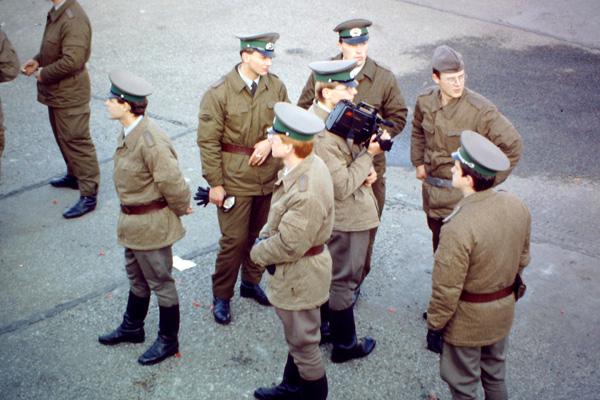 Eine Gruppe von jungen NVA Soldaten steht auf einem Platz in Berlin und schaut in unterschiedliche Richtungen. Einer von ihnen trägt eine Videokamera.