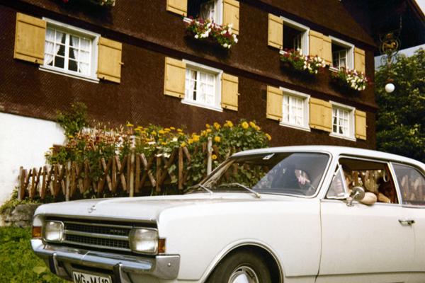 Menschen sitzen in einem weißen Opel vor einem hölzernen Haus mit Blumen vor den Fenstern.