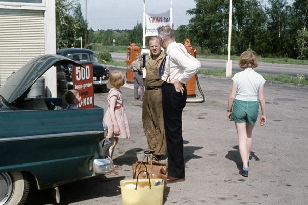 Eine Familie macht Halt auf einer Tankstelle und steht vor dem geöffneten Kofferraum ihres Autos.
