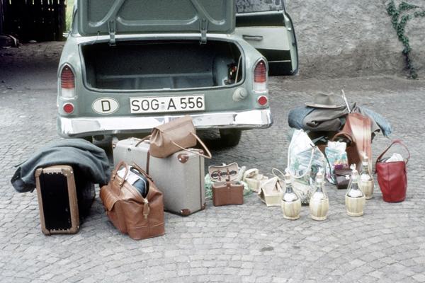 Gepäck steht vor einem Auto (Opel Rekord)  mit offenem Kofferraum vor einem Hotel in Lovran. Unter dem Gepäck sind auch Rotweinflaschen.