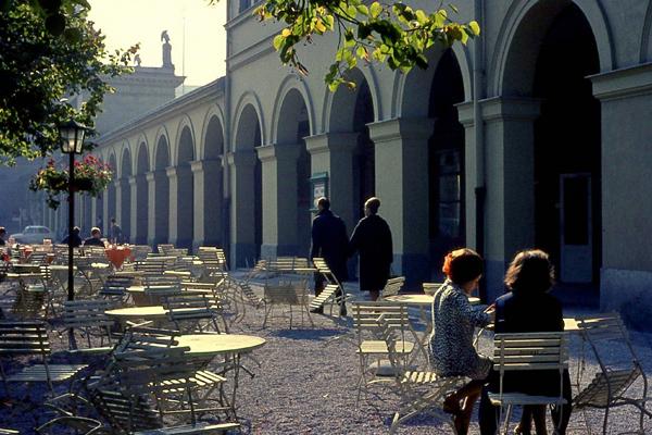 Im Spätsommer sitzen Menschen auf Gartenstühlen vor den Arkadengängen im Hofgarten in München.