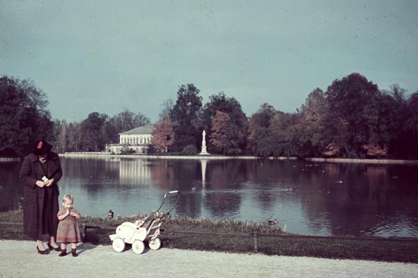 Eine Mutter steht mit ihrem Kind und Kinderwagen an einem Gewässer im Schlosspark Nymphenburg. Im Hintergrund ist ein Teil der Schlossanlage zu sehen.