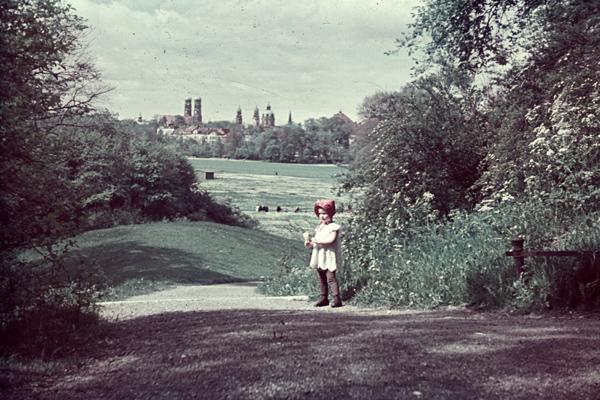 Ein Mädchen mit Pusteblume in der Hand steht im Englischen Garten in München. Blick vom Monopteros auf die Frauenkirche und Theatinerkirche.
