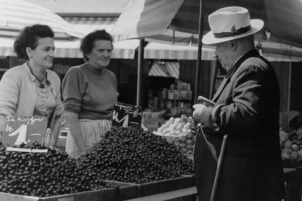 Ein Mann sieht sich Kirschen auf dem Viktualienmarkt in München an.