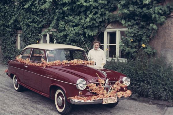 Eine Junge Frau steht bei einem roten Borgward Isabella. Das Auto ist mit roten und orangenen Blumen geschmückt.
