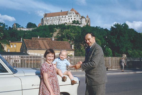 Ein Familienvater posiert mit seinen Kindern vor der Burg Trausnitz in Landshut. Links im Bild eine Borgward Isabella. Aufnahme von 1956.