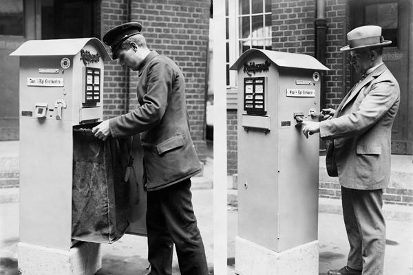 Briefkästen der Reichspost mit einem Automaten für den Verkauf von Briefmarken. Rechts ist zu sehen, wie ein Kunde den Automaten bedient, links einen Postboten beim Leeren des Briefkastens.