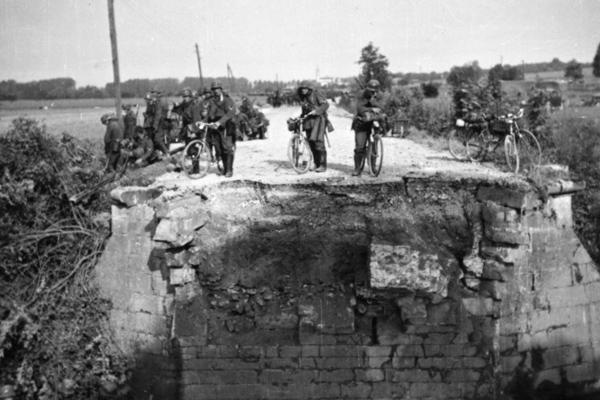 Deutsche Soldaten stehen mit ihren Fahrrädern vor einer gesprengten Brücke in der Normandie während des Zweiten Weltkrieges.