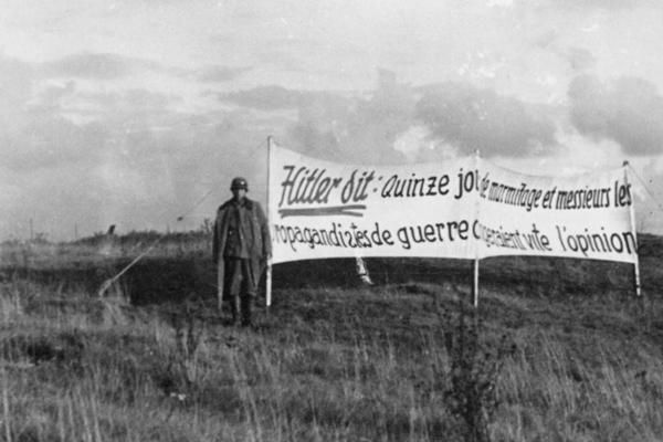 """Ein deutscher Soldat steht vor einem Propagandaplakat, auf dem auf Französisch steht """"Hitler sagt: Zwei Wochen dauerhaftes Bombardement und die Herren Kriegspropagandisten werden schnell ihre Meinung ändern."""" auf einem Feld in Frankreich."""
