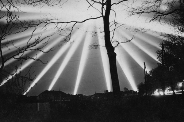 Flakscheinwerfer erhellen den Nachthimmel zum Aufspüren von  feindlichen Flugzeugen während des Zweiten Weltkrieges.