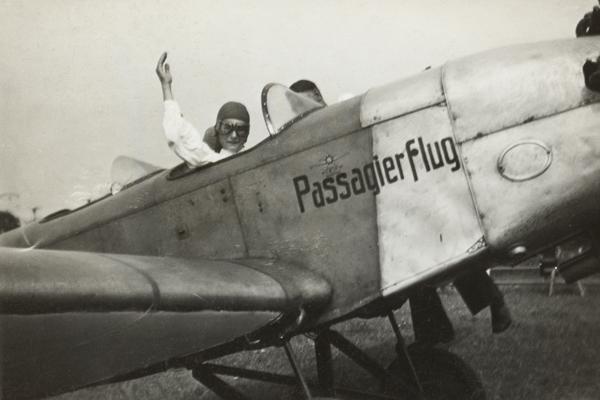 Frau winkt aus einem Passagierflugzeug (undatierte Aufnahme).