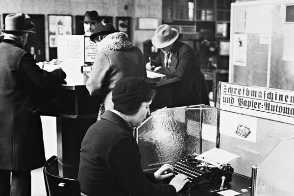 Im Postamt Charlottenburg I. wurde im Schalterraum ein Schreibmaschinen- und Papier-Automat, der gegen Einwurf von 10 Pfenning Papier liefert und die Schreibmaschine für kurze Zeit zum Schreiben frei macht, aufgestellt. Im Hintergrund Kunden an einem Schreibpult.