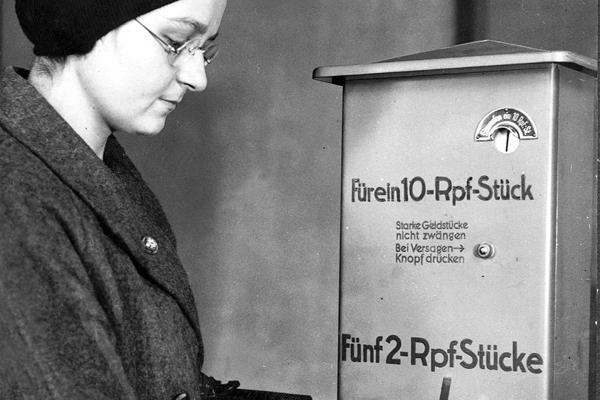 Eine Frau bedient einen Geldwechselautomaten, der ein 10-Reichspfennig-Stück in fünf 2-Reichspfennig-Stücke wechselt.