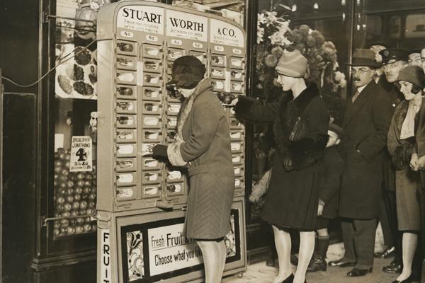 Kundinnen und Kunden stehen vor einem Automaten in der Liverpoolstreet, an dem frisches Obst in Papiertüten ziehen kann.