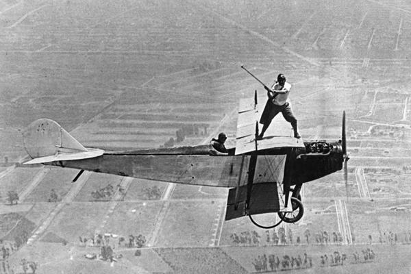 Ein Mann spielt auf den Tragflächen eines fliegenden Fugzeuges Golf in 1000 Meter Höhe.