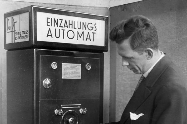 In Banken und Sparkassen soll ein Automat aufgestellt werden, der die umständlichen Zahlungsformalitäten vereinfacht. Gegen Einwurf eines Zehnpfennigstücks dispensiert der Automat ein Kuvert und eine Metallmarke. Das Kuvert ist zur Aufnahme des einzuzahlenden Geldes bestimmt und mit einer Kontrollnummer versehen. Diese Kontrollnummer befindet sich auch auf dem Abschnitt des Kuverts, den der Kunde zurückbehält. Nach Einlage des Geldkuverts wird die Metallmarke in den zweiten Schlitz geworfen. Daraufhin öffnet sich die Einwurfstelle für das Kuvert automatisch und das Kuvert fällt in einen Panzertresor. Dieser Tresor wird täglich durch zwei Angestellte des Sparinstituts geleert, die die Beträge zur Gutschrift abholen. Der Kontrollabschnitt dient als Legitimation für den Einzahler bei nachträglicher Eintragung ins Sparbuch.