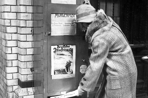 Eine Frau zieht sich an einem Berliner Bahnhof eine Zeitung aus einem Zeitungsautomaten.