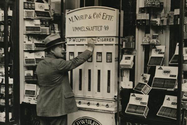Ein Kunde zieht an einem Automaten vor einem Tabakladen Zigaretten.