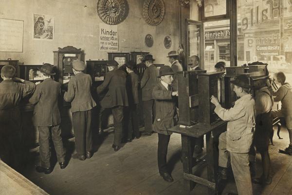 Eine der ersten Spielautomatenhallen, in der mit einem Einsatz von 10 Pfennig Glücksspielautomaten betrieben werden konnten. Obwohl Jugendlichen unter 16 Jahren der Eintritt streng verboten ist, wie aus dem aufgehängten Plakat hervorging, kümmert sich hier keiner der hier spielenden Jugendlichen um das Verbot.
