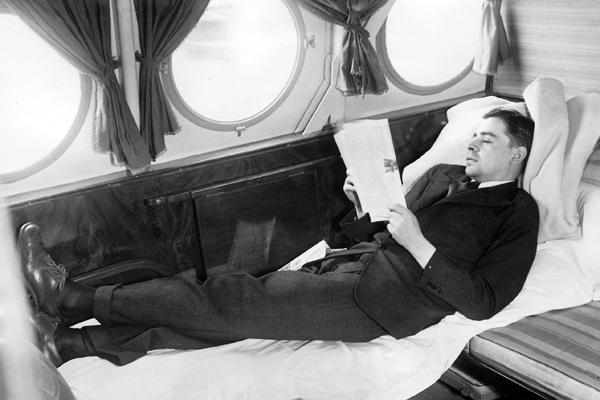Während der langen Flüge der Flugboote vom Typ Dornier X über den Atlantik sollten die Passagiere auch schlafen können. Ein Passagier demonstriert ein sog. 'Pullmann-Bett' in einer Kabine eines Flugbootes.