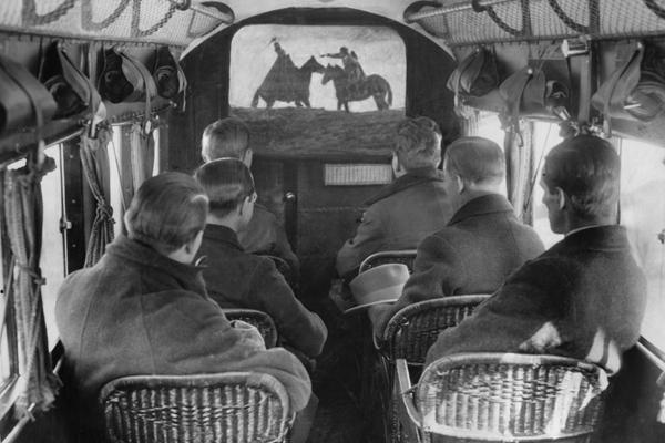 Männer sitzen in Korbstühlen in einem Flugzeug und schauen einen Film.(Kinoleinwand retuschiert.), 01.01.1925-31.12.1925