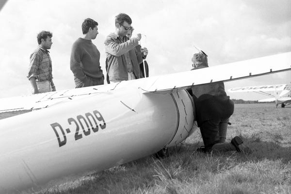 Eine Gruppe von Menschen wartet ein Flugzeug. Vermutlich bei Berlin, 1968.