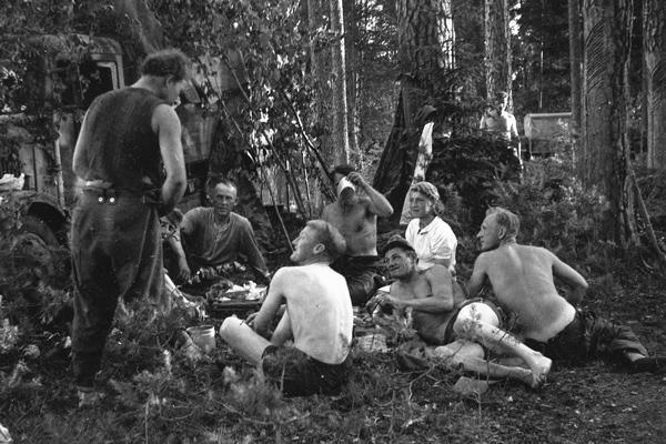 Soldaten biwakieren im Wald. Sie sind fröhlich und essen. Eine Frau sitzt bei der Gruppe.  Das Bild wurde durch einen Angehörigen des 154. Infanterieregiments / 58. Infanteriedivision, in Frankreich aufgenommen.