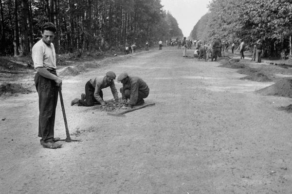 Unter Bewachung wird eine Straße in Frankreich von Zivilisten repariert.  Das Bild wurde durch einen Angehörigen des 154. Infanterieregiments / 58. Infanteriedivision, in Frankreich aufgenommen.