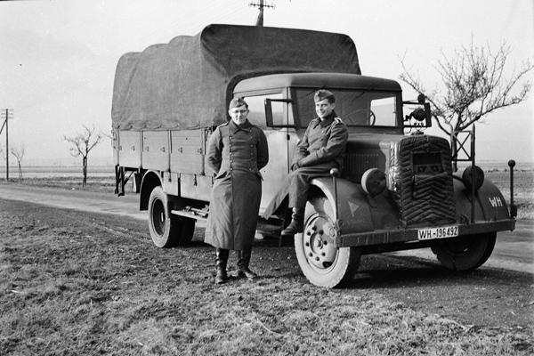 Ein Unteroffizier sitzt auf dem Kotflügel eines MAN LKWs. Ein weiterer Soldat steht daneben. Das Bild wurde durch einen Angehörigen des Radfahrgrenadierregiment 2 / Radfahrsicherungsregiment 2, an der Ostfront aufgenommen. Vermutlich während der Zeit des Vormarschs im Sommer 1941
