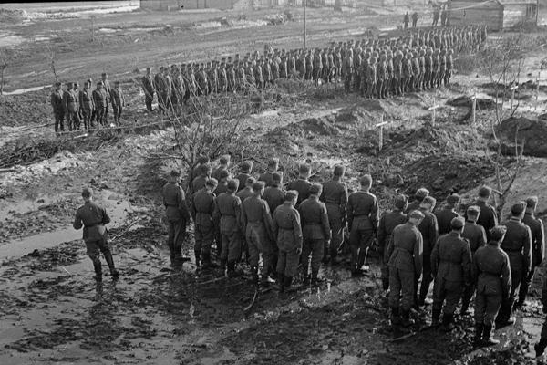 Deutsche Soldaten sind zum Massenbegräbnis angetreten. Das Bild wurde durch einen Angehörigen des Radfahrgrenadierregiment 2 / Radfahrsicherungsregiment 2, im Nordabschnitt der Ostfront aufgenommen.