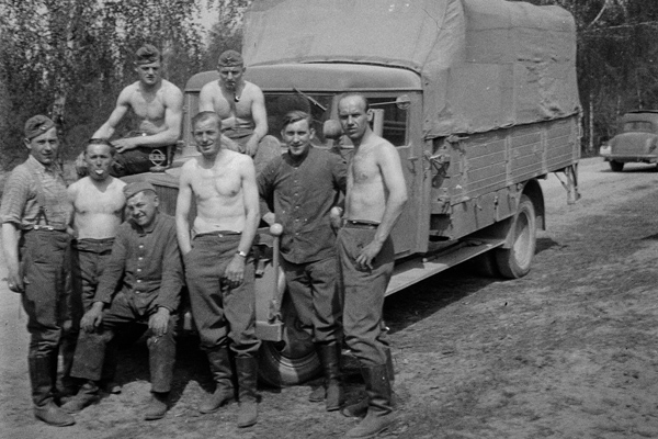 Soldaten gruppieren sich, oberkörperfrei, in der Sonne vor dem Laster. Das Bild wurde durch einen Angehörigen des Radfahrgrenadierregiment 2 / Radfahrsicherungsregiment 2, im Nordabschnitt der Ostfront aufgenommen.