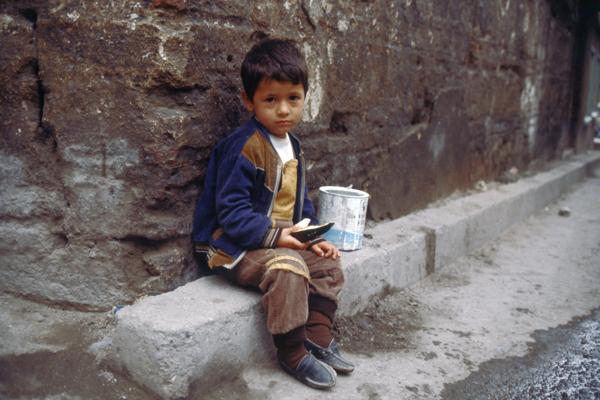 Ein Kind sitzt im istanbuler Altstadtviertel Eminönu vor einer Mauer.