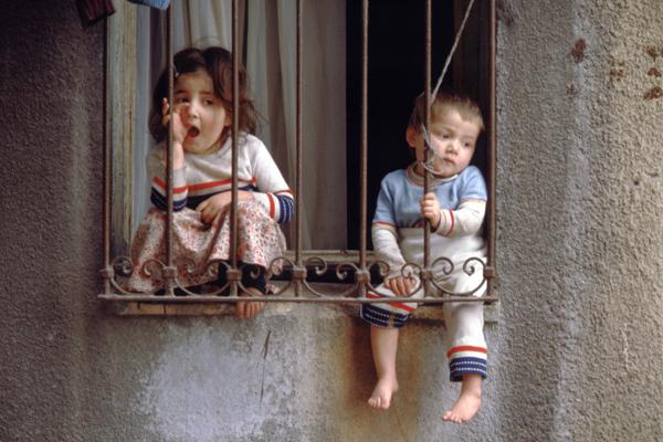Zwei kleine Kinder sitzen auf einer Fensterbank im Altstadtviertel Eminönu in Istanbul. Das Fenster ist vergittert.