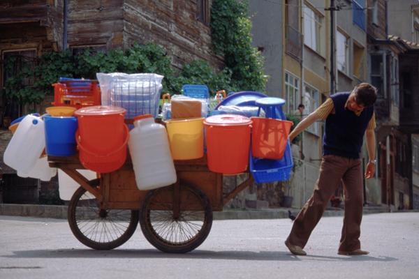 Ein Straßenhändler im Altstadtviertel Eminönu in Istanbul geht mit seinem Wagen über die Straße. An seinen Wagen sind verschiedene Plastikbehälter und waren gehangen, die er zum Verkauf anbietet.