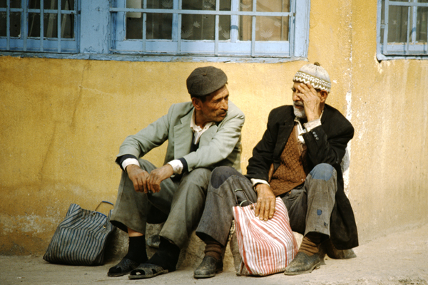 Zwei Männer sitzen am Boden und unterhalten sich im Altstadtviertel Eminönu in Istanbul.