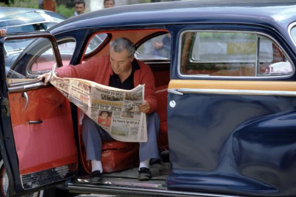Ein Wartender Taxifahrer sitzt in seinem Auto und liest Zeitung in Istanbul im Stadteil Üksüdar.