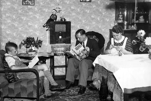 Eine Familie sitzt im Wohnzimmer vor einem Radio, der Mann liest die 'Europastunde', der Junge ein Buch und die Frau strickt.