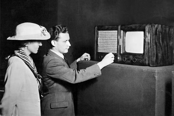 Auf der Berliner Funkausstellung wird einer Frau von einem Herren ein sogenanntes 'Heimfernsehgerät' vorgeführt.