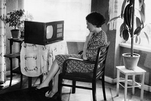 Eine Frau sitzt vor ihrem Fernsehgerät und sieht sich das Programm an.