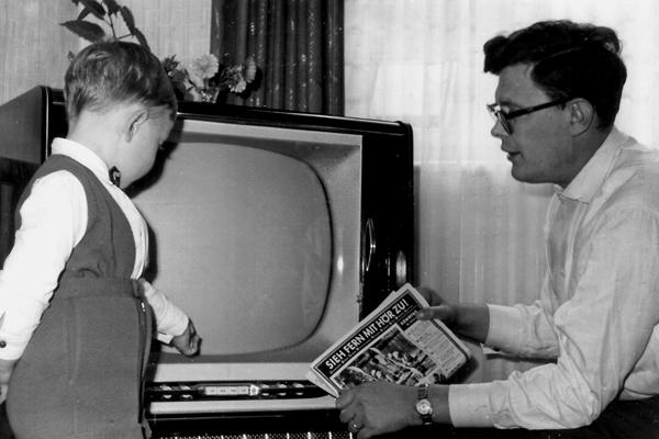 Ein Vater mit Sohn vor einem Fernsehgerät hät in der Hand eine Fernsehzeitschrift.