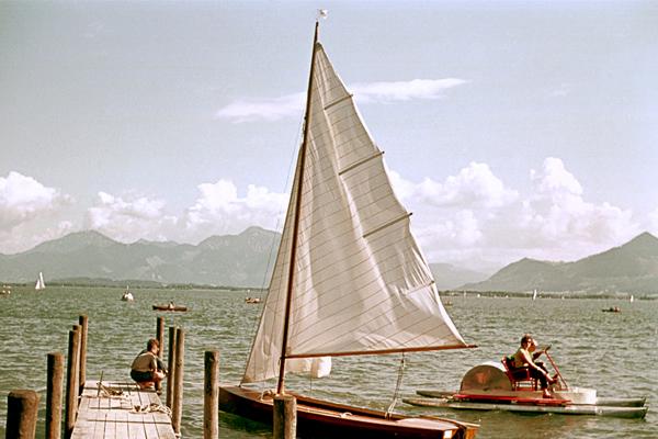 Bootssteg am Chiemsee mit Segelboot und Tretboot.