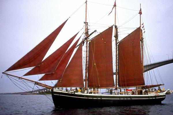 Ein Dreimastschoner in der dänischen Ostsee. Die Segel des Schiffes sind rot.