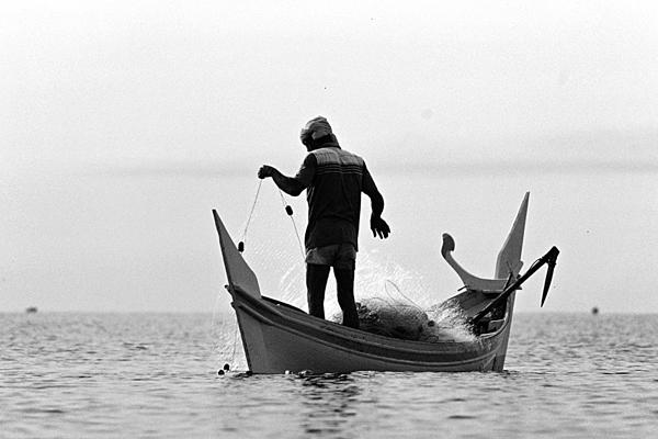 Ein Fischer in seinem Boot auf dem Wasser in Malaysia. Er holt das Netz ein.
