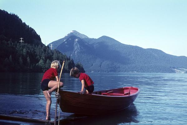 Kinder spielen am Ufer mit einem Ruderboot
