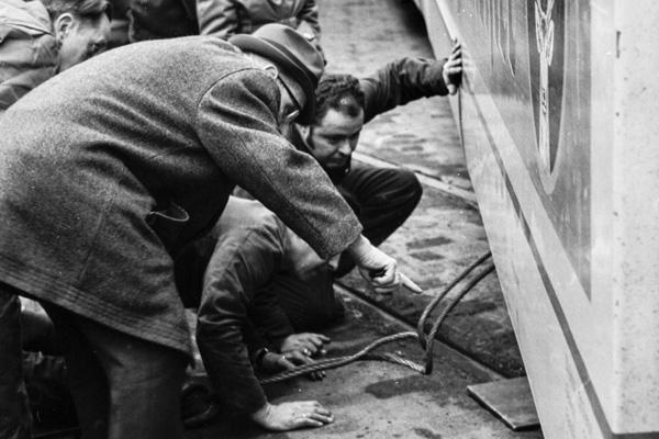 Ein Junge und ein Schaffner schauen den Arbeitern zu, wie die Straßenbahn wieder auf die Gleise gebracht wird.