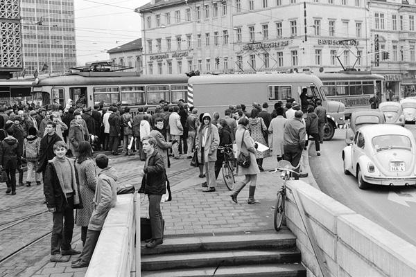 Während im Hintergrund eine entgleiste Straßenbahn wieder auf die Schienen gezogen wird, schlängelt sich der Verkehr vorne ohne die Anwesenheit von Polizisten vorbei.