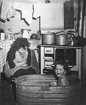 Szene in einfacher Wohnungsküche Anfang der 50er-Jahre. 6-jähriges Mädchen sitzt in Zinkbadewanne, daneben seine Mutter. Einfachste Küchenausstattung mit Kohleherd - so wie damals häufig.